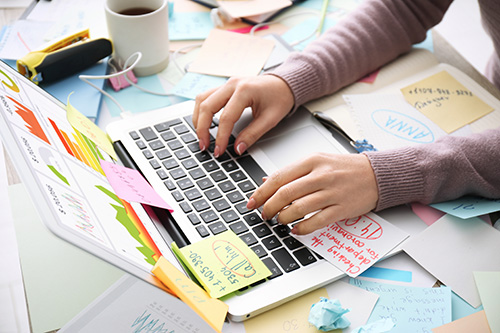 Hände am Laptop. Viele Post it mit Arbeit verkleben alles